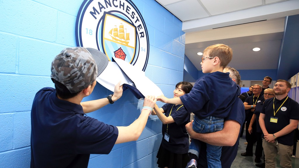 A young Manchester City fan is given a helping hand to reveal the new crest in The Blue's dressing room at the Etihad Stadium