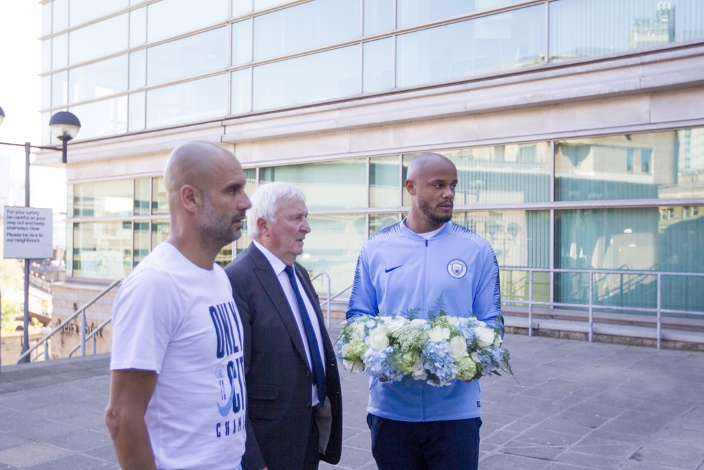THIS CITY REMEMBERS: Pep Guardiola, Mike Summerbee and Vincent Kompany visited the Manchester Arena before the parade to lay a wreath in memory of those who tragically lost their lives one year ago.